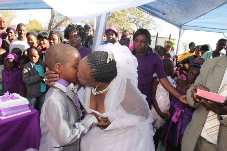 *** EXCLUSIVE *** MPUMAALANGA, SOUTH AFRICA - JULY 12: Groom Sanele Masilela (9) gets a kiss from his bride Helen Shabangu (63) at their second ritual marriage ceremony on July 12, 2014 in Kildare Village, Ximhungwe near Bushbuckridge in Mpumalanga, South Africa. A NINE-YEAR-OLD schoolboy has become one of the worldís youngest grooms for the SECOND time ñ marrying his 62-year-old wife AGAIN. Looking a little taller in last yearís silvery tuxedo, baby faced Saneie Masilela clutched the hand of Helen Shabangu as they repeated their vows one year on. Last year the boy, from nearby Tshwane, tied the knot with bride Helen after claiming he had been told by his dead ancestors to wed. Shockingly his family took the message from the heavens seriously and hurriedly forked out £500 for the bride and a further £1,000 for the big day. The second marriage ceremony was this time held at the home of the blushing bride in Ximhungwe in Mpumalanga, South Africa, in front of around 100 guests. Wide-eyed residents looked on as the MARRIED mother-of-five shared a piece of cake, a toast and even a kiss with her young groom Sanele ñ and long-term husband Alfred Shabangu, 66. PHOTOGRAPH BY Dimakatso Modipa / Barcroft Media UK Office, London. T +44 845 370 2233 W www.barcroftmedia.com USA Office, New York City. T +1 212 796 2458 W www.barcroftusa.com Indian Office, Delhi. T +91 11 4053 2429 W www.barcroftindia.com